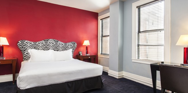 executive suite with red wall, queen bed and a desk
