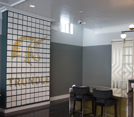 gold hotel trundle and unicorn logo on white tile wall