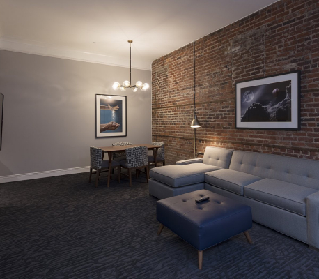 grey couch against a brick wall