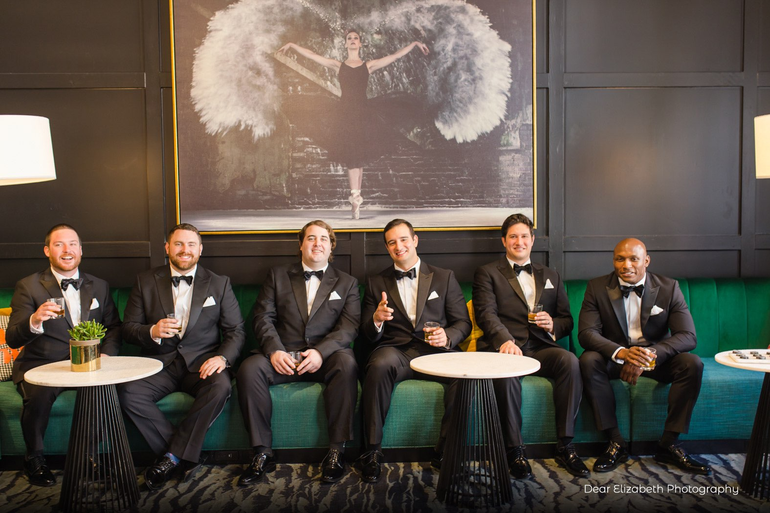 groomsmen sitting and laughing on a couch
