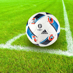 Adidas soccer ball from Euro 2016 on green grass with white chalk corner lines