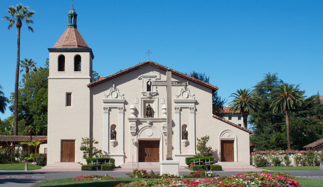 Mission Santa Clara de Asis with blue sky vibrant colorful flowers and palm trees