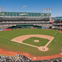 Oakland Coliseum baseball park on a sunny day. No clouds in the sky and the park is full of fans