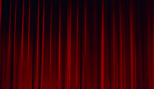 closed red curtain on a theater stage