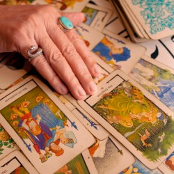 Hand spreading tarot cards on a table
