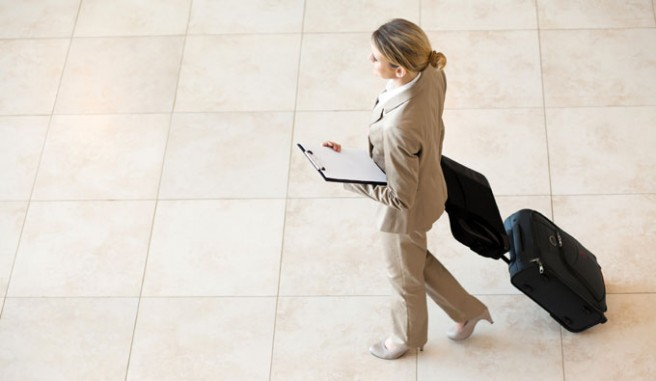 business women, in tan pant suit, walking with suitcase Header