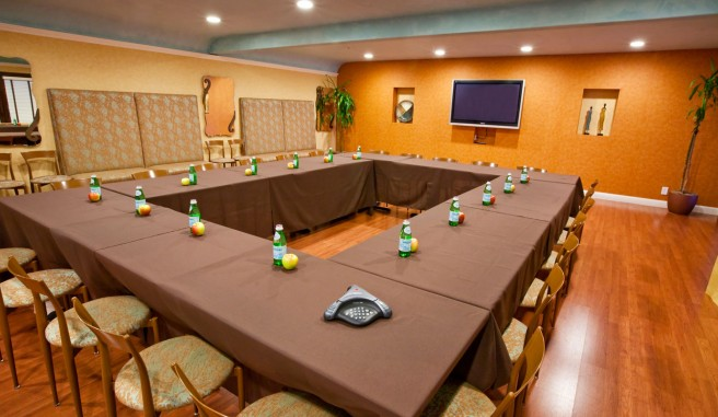 meeting space with large television. Meeting tables arranged in large square. Seating all facing in