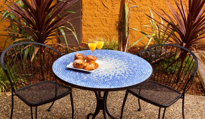outdoor blue mosaic cafe table with 2 chairs housing croissants and orange juice