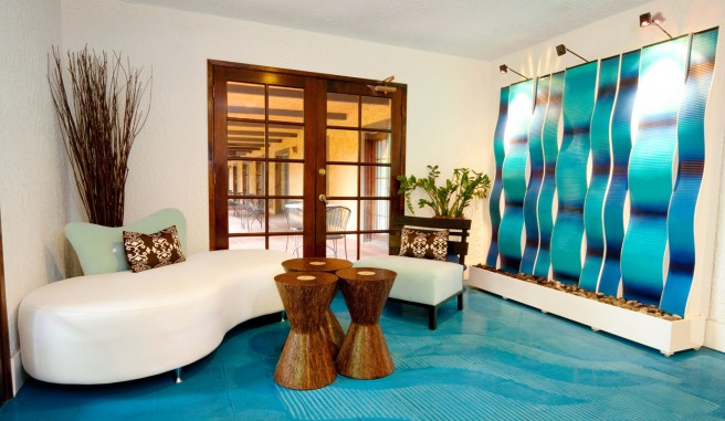 loby, with sleek white leather seating area. Aqua blue carpeting and Water inspired wall art instillation