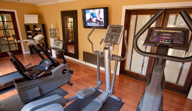 gym with a number of cardio machines, a television, water cooler and large french doors