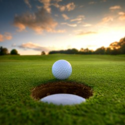 golf ball near hole with sunsetting