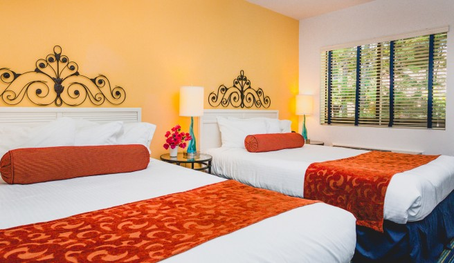 double bed room, white sheets, bright terracotta colored walls and accent blankets.