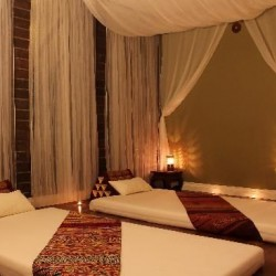 thai massage room contains draped lined walks. Warm dim lighting and exotic lined mats for a couples massage