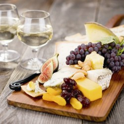 fruit and cheese board with 2 glasses of white wine