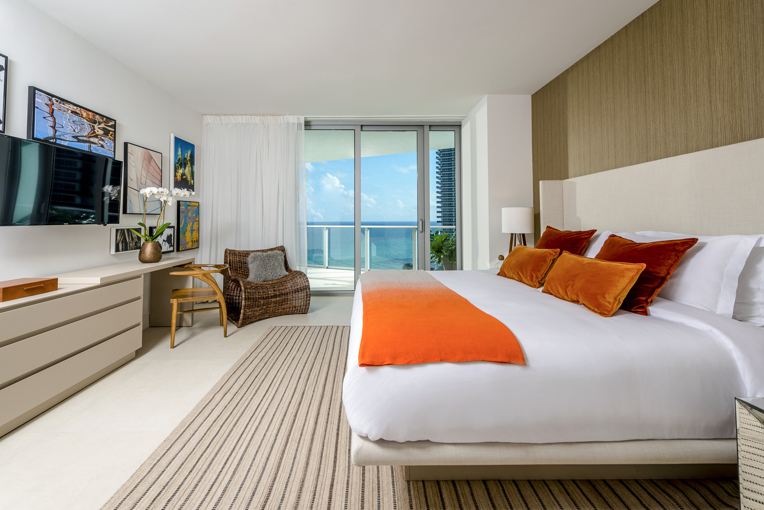 one bedroom suite, with dresser and desk. Mounted TV and queen sized bed, balcony with ocean view