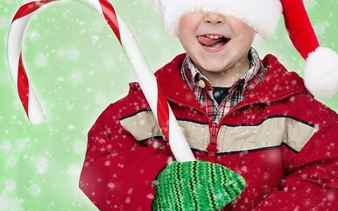 Boy in Santa Hat Holding Giant Candy Cane