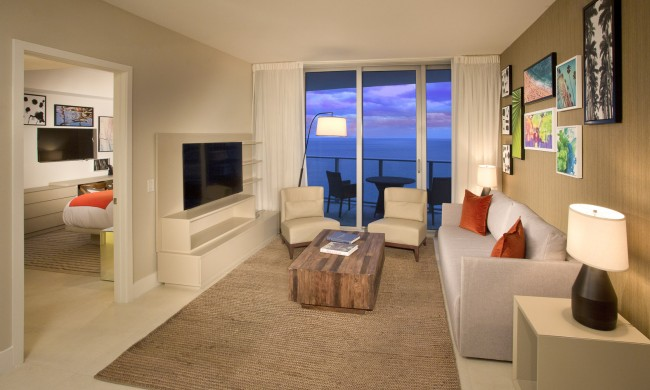 1 bedroom ocean view living room. Couch and 2 chairs, television mounted on the wall, adjacent room