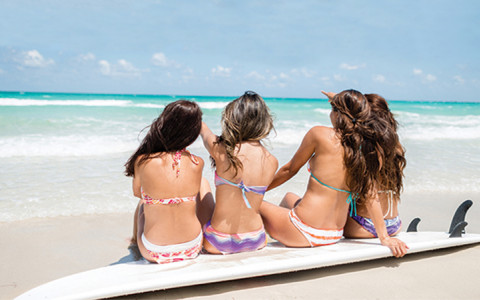 4 girls sitting on a surfboard on the beach
