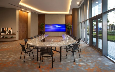 Caribbean Meeting Room has large u shaped table, large triple screen tv. ;large floor to ceiling windows and entrance to exterior