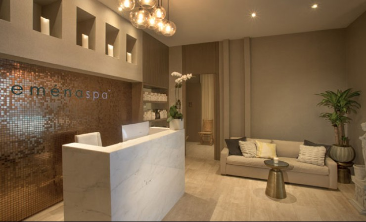 Emena Spa Lobby with marble front desk and tiled wall with couch seating area adjacent