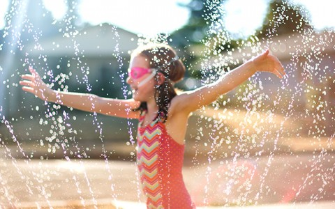 little girl playing in sprinkler water