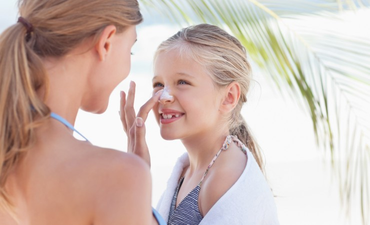 Mom putting sunscreen on daughter's nose