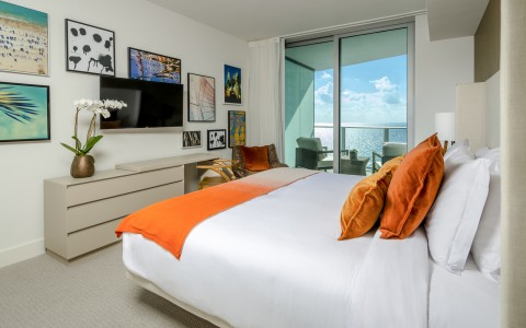 One Bedroom Suite, with dresser, desk, mounted tv, queen size bed, balcony with ocean view