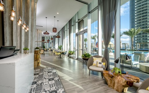 Terrazas lobby. Off from the pool has a wall of windows marble and wood tones and textures throughout. There are a number of sitting areas and dining tables