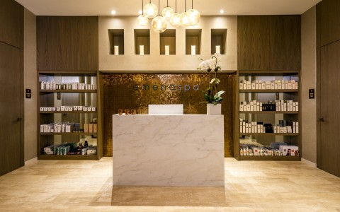Emena Spa Lobby with large marble front desk with a wall of products displayed behind.