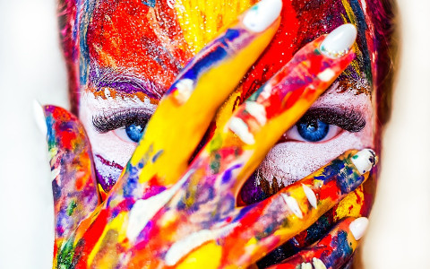 Woman Painted in Multiple Bright Colors Holding Hand Up in Front of Face