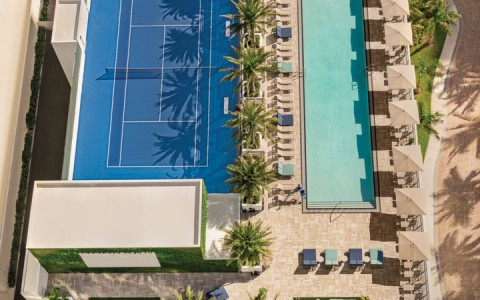 Aerial view of pool next to tennis court