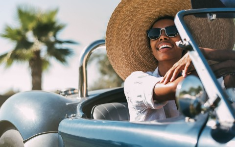 Woman in sunhat driving car