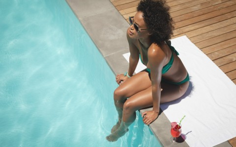 Woman sitting at edge of pool