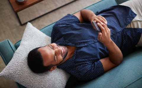 Man laying down on a couch while looking at phone
