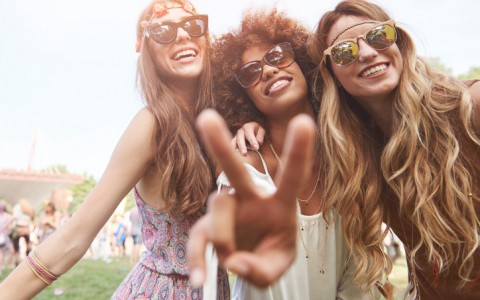 three young women having fun at a music festival wearing sunglasses and flower crowns
