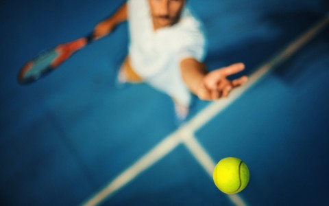 shot from above of a man about to serve a tennis ball