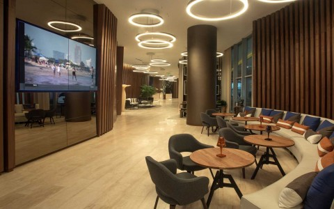 lobby entrance is very sleek and modern. High ceilings with modern circular light fixtures. Long seating area lines the entrance wall and TV's display images on the wall