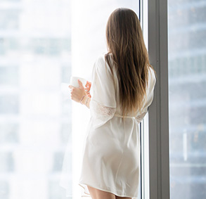 Woman in robe next to window