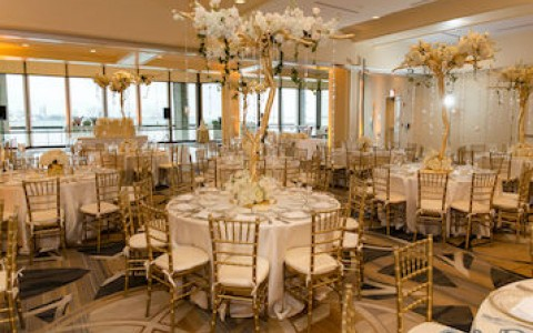 Ballroom with tables, chairs and floral centerpieces