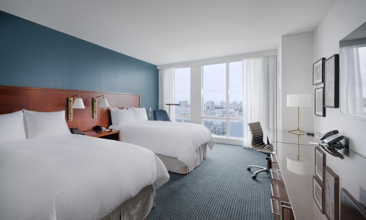 guest room with two double beds, desk, area, and floor to ceiling windows overlooking the city
