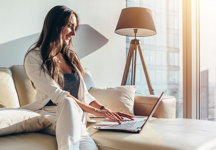 woman sitting on a couch working on her laptop