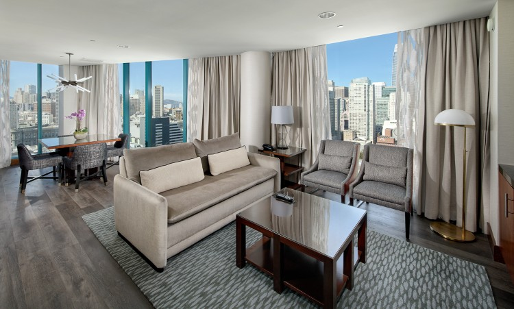 modern living room area in a suite with windows all around overlooking the city