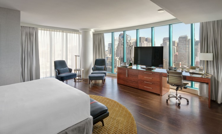 suite with a large bed, tv, and a view of the city