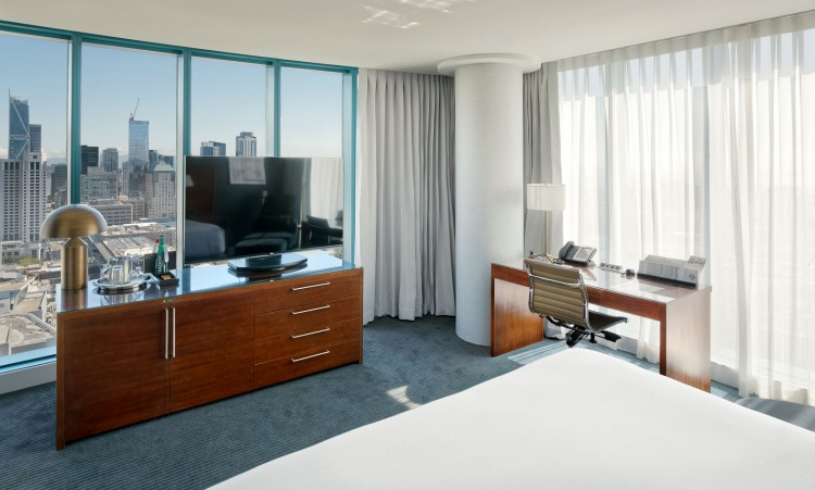 large room with a bed, tv, and a view of the city