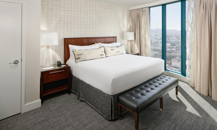 big hotel room with a large bed and view of the city