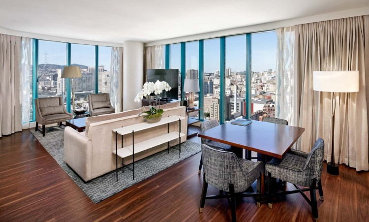 guest room suite living area with dining table, couch, chairs, wooden floors, and windows looking out onto the city