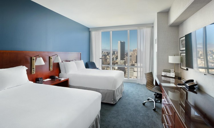 large room with two big beds and a view of the city