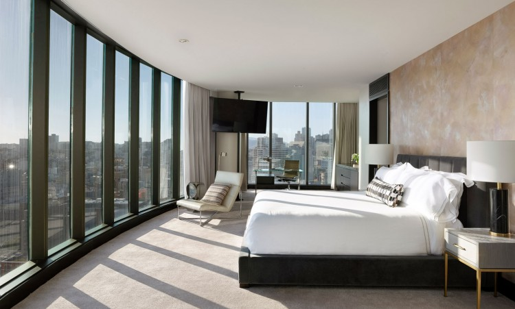 large room with a huge bed, chair to relax in, and a view of the city