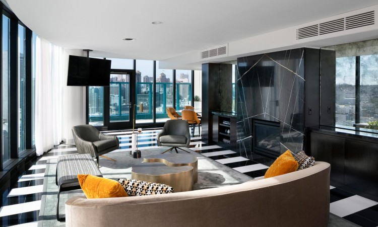 lounge area with chairs, tv, and a view of the city