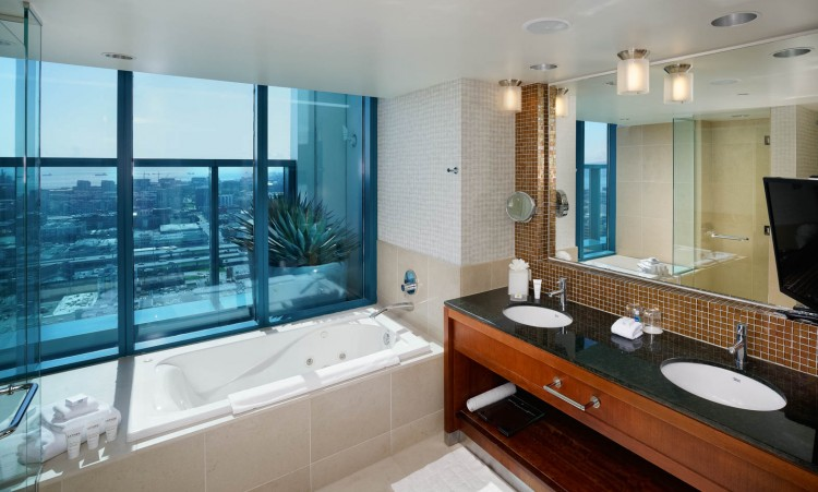 fancy bathroom with huge sink space and big windows with a view of the city